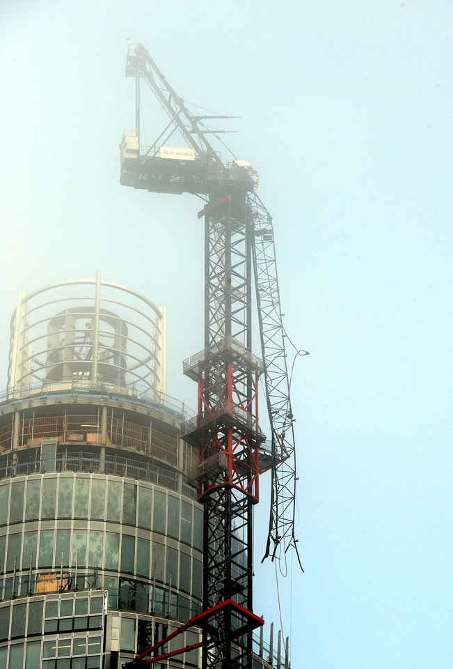 Photo - A general view of the damaged crane on top of St Georges Tower close to the scene where a helicopter crashed in central London, Wednesday Jan. 16, 2013. Police say two people were killed when a helicopter crashed Wednesday during rush hour in central London after apparently hitting a construction crane on top of a building. (AP Photo/PA, John Stillwell) UNITED KINGDOM OUT  NO SALES  NO ARCHIVE