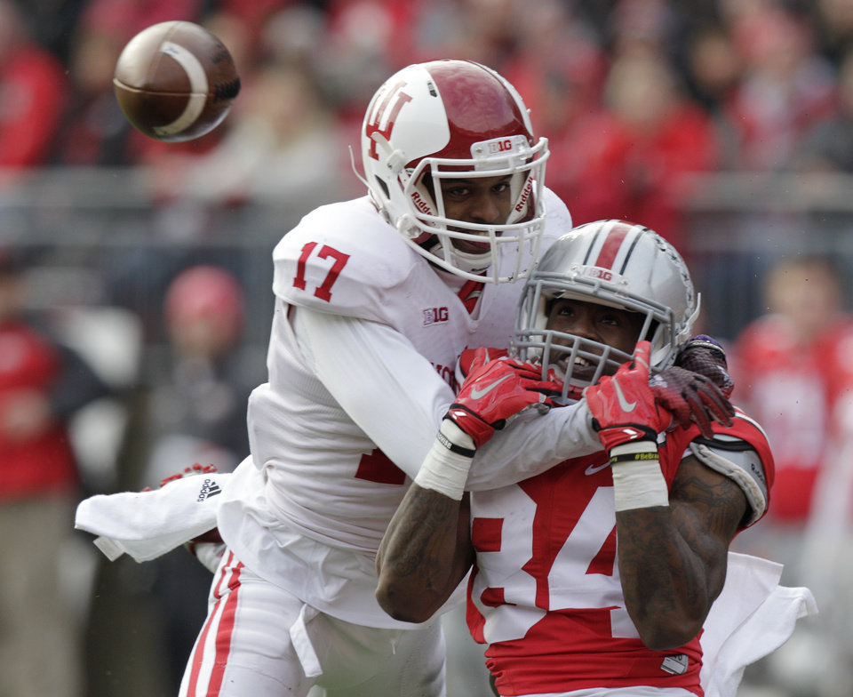 Photo - Indiana cornerback Michael Hunter, left, breaks up a pass intended for Ohio State wide receiver Corey Smith during the third quarter of an NCAA college football game Saturday, Nov. 22, 2014, in Columbus, Ohio. Ohio State beat Indiana 42-27. (AP Photo/Jay LaPrete)