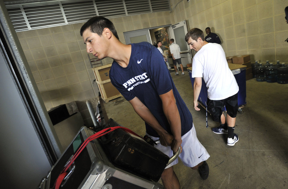 Photo - Penn State team managers Nick Venturino, left, and Evan Tucker, right, load equipment to be shipped to Ireland, in University Park, Pa., Tuesday, Aug. 26, 2014.  Penn State plays Central Florida in the Croke Park Classic, in Dublin, Ireland, this Saturday.     (AP Photo/Centre Daily Times,Nabil K. Mark    MANDATORY CREDIT; MAGS OUT