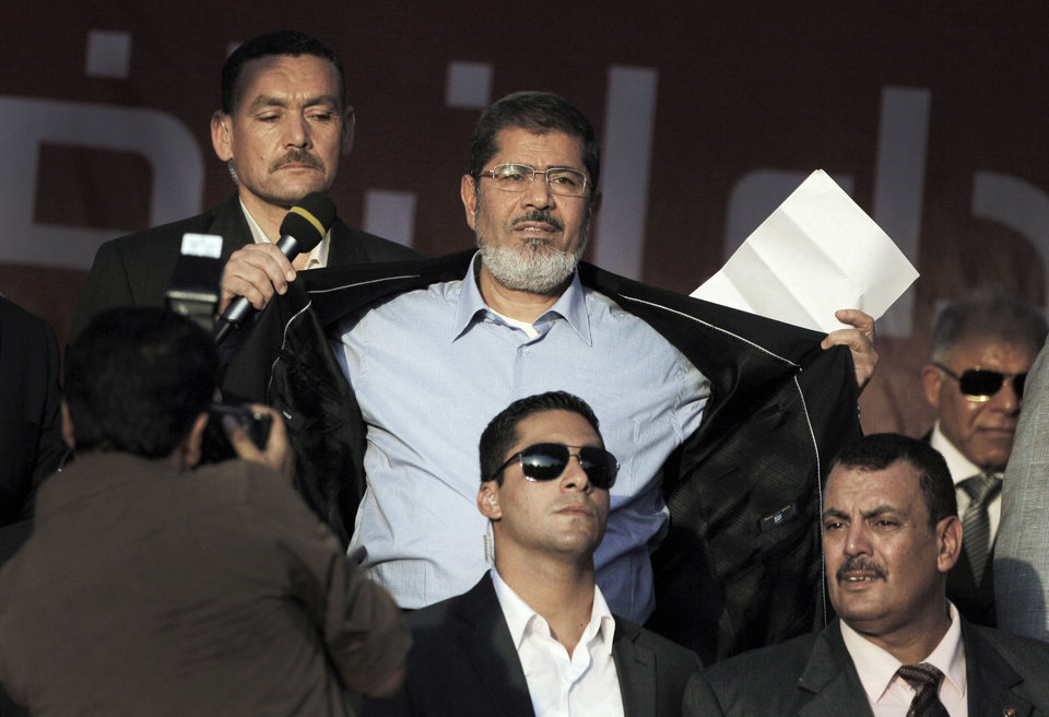 Photo -   FILE - In this Friday, June 29, 2012 file photo, Egypt's President-elect Mohammed Morsi opens his suit jacket to show his supporters that he is not wearing body armor at Tahrir Square, the focal point of Egyptian uprising, during his speech in Cairo, Egypt. The message is clear: Morsi has nothing to fear because he sees himself as the legitimate representative of Egypt's uprising. His speeches reveal a populist bent, making generous promises that many are skeptical he can keep. And though he began as an awkward and uninspiring speaker, he appears to be striving to reinvent his decidedly uncharismatic public persona. (AP Photo/Amr Nabil, File)