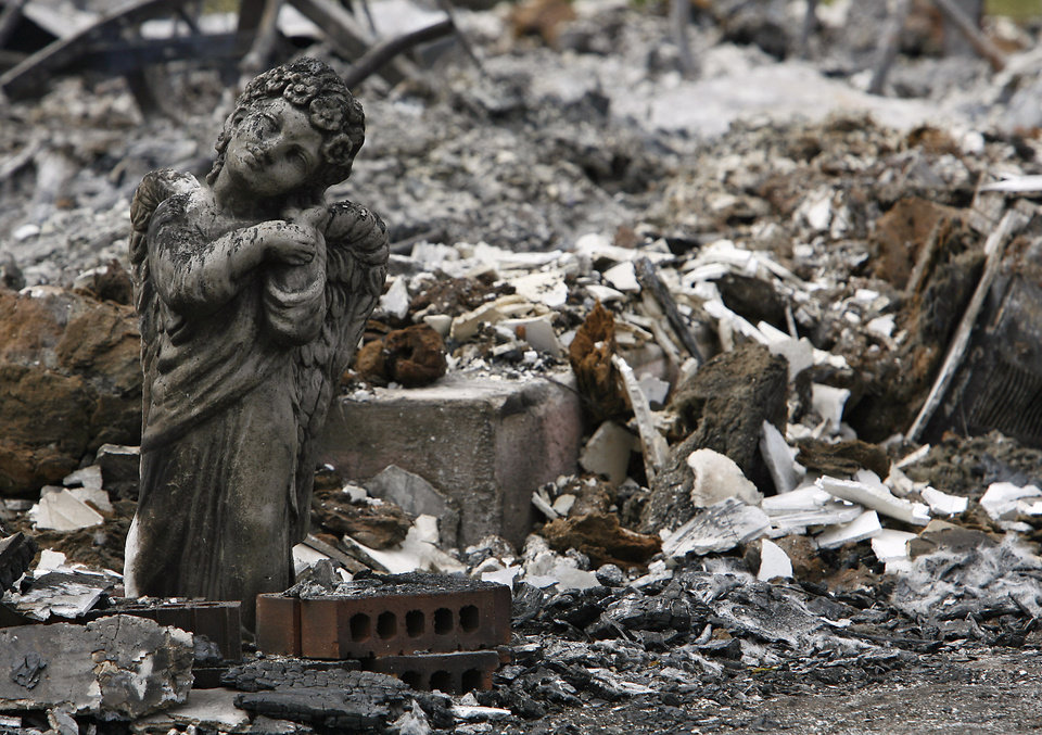 A soot covered angel statue still stands outside a house that was destroyed by wildfires on Friday, April 10, 2009, in Choctaw, Okla.  Photo by Chris Landsberger, The Oklahoma