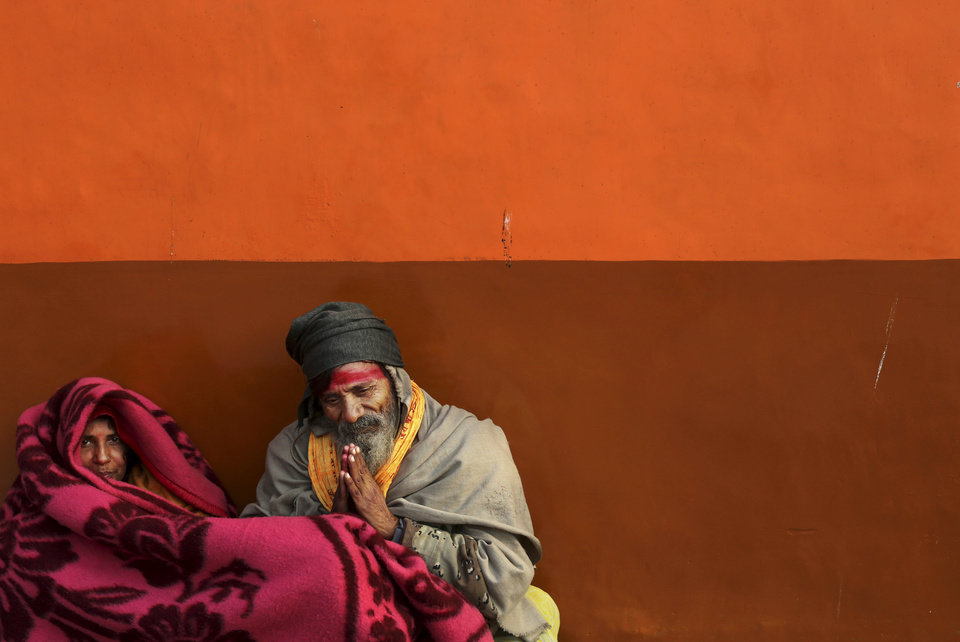 Indian Hindu worshippers are wrapped in blankets as they try to stay warm on a cold winter morning outside a temple in New Delhi, India, Tuesday, Jan. 8, 2013. North India continues to face below average weather conditions with dense fog affecting flights and trains. More than 100 people have died of exposure as northern India deals with historically cold temperatures. (AP Photo/Kevin Frayer)
