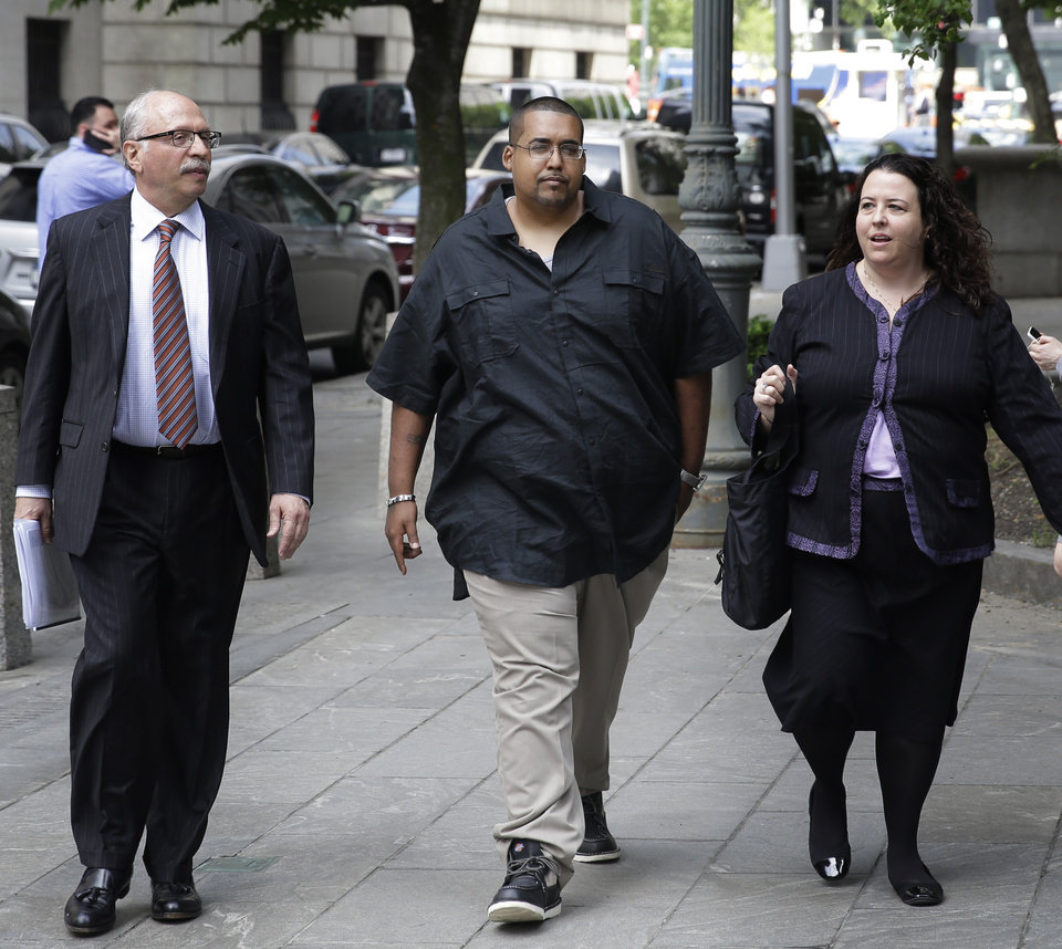 Photo - Hector Xavier Monsegur, flanked by members of his legal team, arrives at court in New York for a sentencing hearing Tuesday, May 27, 2014. Monsegur, a prolific computer hacker who infiltrated the servers of major corporations, later switched sides to helped the U.S. government disrupt hundreds of cyberattacks on Congress, NASA and other sensitive targets, according to federal prosecutors. After his arrest and guilty plea in 2011, he faced more than two decades behind bars. But because of his cooperation, the sentence could be two years or less.  (AP Photo/Seth Wenig)