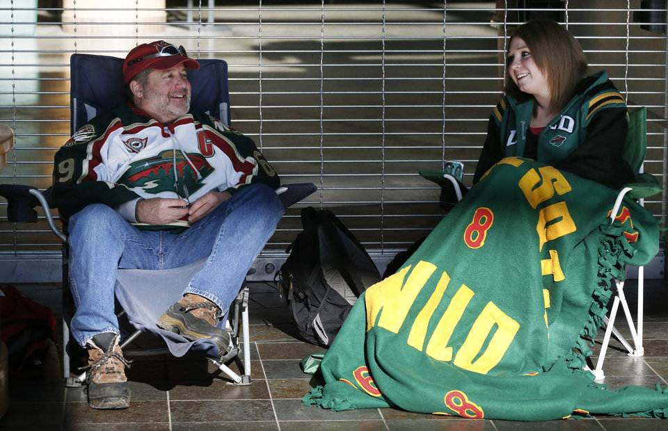 Photo - FILE - In a Tuesday, Jan. 15, 2013 file photo, Minnesota Wild hockey fans Pat Vos, left, and Jess Crane marked their spots, first and second respectively, for Wild tickets at the Xcel Arena in St. Paul, Minn. The lockout that lasted 119 days has ended, the new collective bargaining agreement is in place and the NHL is finally about to play games again after hastily arranged week-long training camps around the league.  (AP Photo/Jim Mone, File)