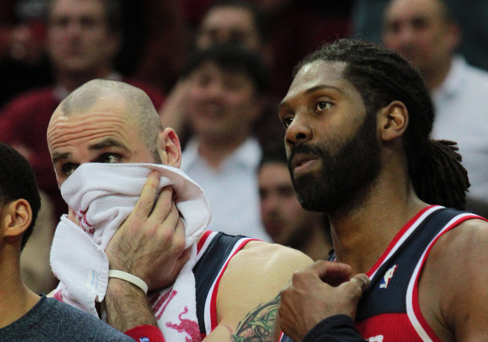 Photo - Washington Wizards Martin Gortat, left, and forward Nene, right, watch from the bench as their team loses to the  Houston Rockets 113-112 in the final seconds of an NBA basketball game in Houston, Wednesday, Feb. 12, 2014. (AP Photo/Richard Carson)