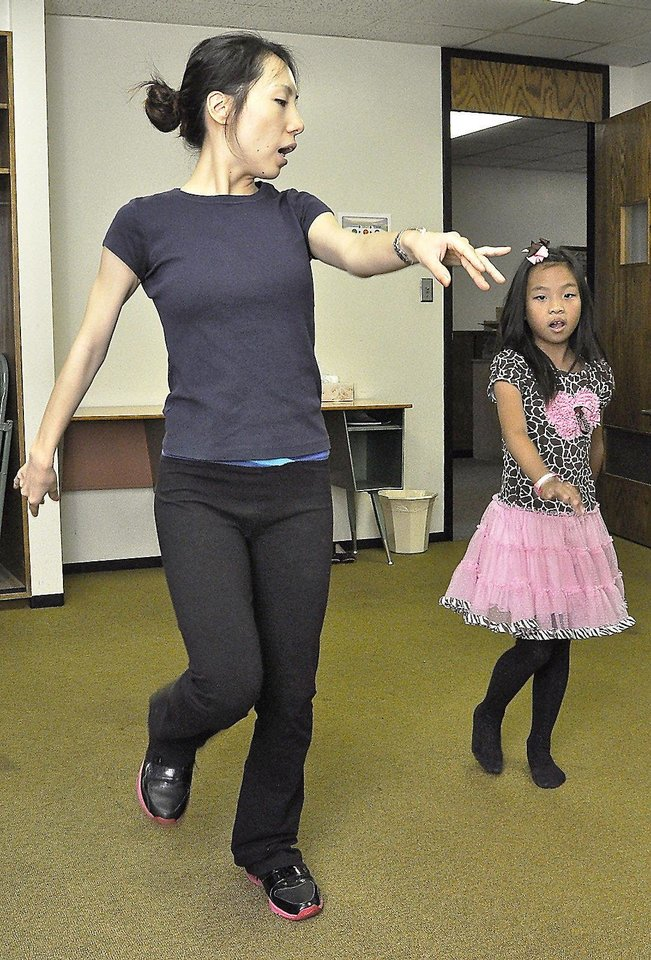 Photo - Sue Xu, Chinese Folk Dance instructor, demonstrates a dance move for Bella Tai, 7, of Oklahoma City during Chinese culture classes at Trinity International Baptist Church Sunday, October 6, 2013. Photo by M. Tim Blake, for The Oklahoman