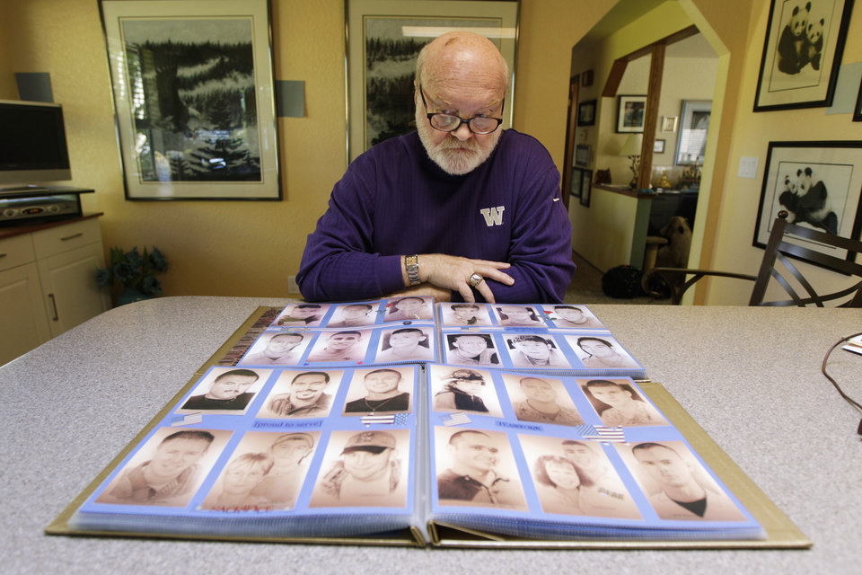 Artist Michael Reagan poses for a photo with two of the many scrap books he has bearing copies of the hand-drawn portraits he has produced of men and women who have been killed at war as he sits in his home, Thursday, Oct. 4, 2012, in Edmonds, Wash. Since starting the Fallen Heros Project in 2004, Reagan has drawn more than 3,000 portraits and given them free-of-charge to the families of the fallen soldiers. (AP Photo/Ted S. Warren)