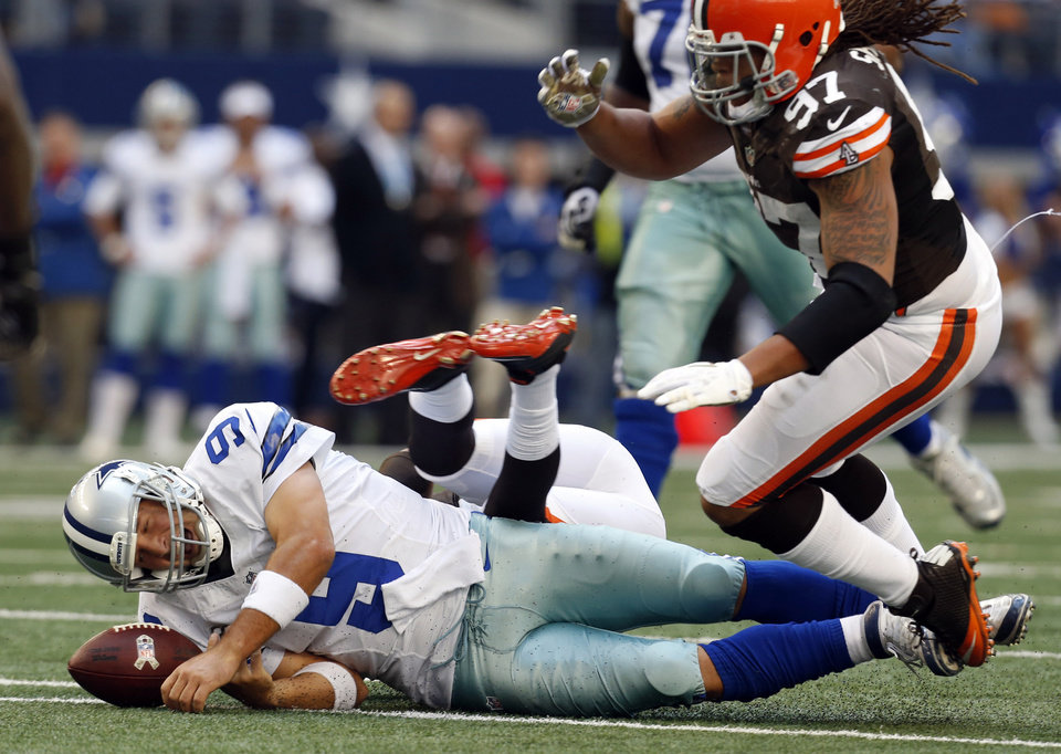 Photo -   Dallas Cowboys' Tony Romo (9) momentarily loses control of the ball after being brought down by Cleveland Browns' Trevin Wade, center back, and Jabaal Sheard (97) in the second half of an NFL football game on Sunday, Nov. 18, 2012, in Arlington, Texas. Romo recovered the ball. (AP Photo/Sharon Ellman)