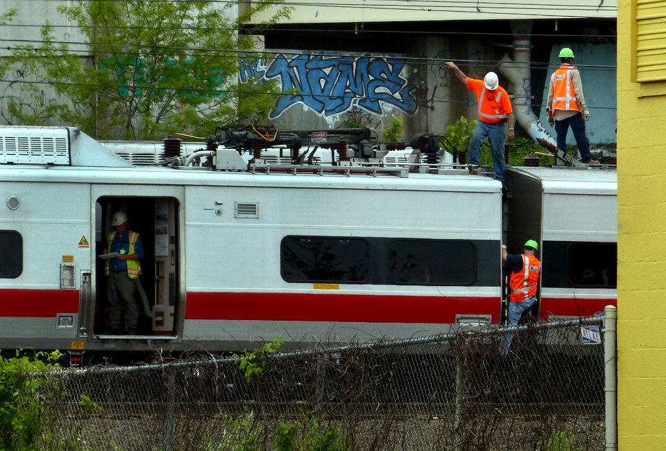 Metro-North Railroad employees work at the scene of the train derailment, Saturday, May 18, 2013 in Bridgeport, Conn. Officials described a devastating scene of shattered cars and other damage where two trains packed with rush-hour commuters collided in Connecticut, saying Saturday it's fortunate that no one was killed and that there weren't even more injuries. (AP Photo/The Connecticut Post, Christian Abraham) MANDATORY CREDIT