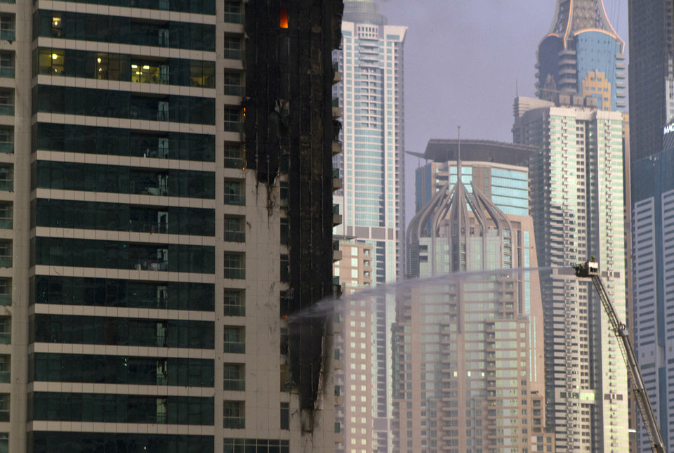 Firefighters spray water on Tamweel residential tower after a fire gutted portions of the building at Jumeirah Lakes Towers, in Dubai, United Arab Emirates, Sunday, Nov. 18, 2012. Civil defense officials did not give immediate details on possible casualties or the cause of the predawn fire. (AP Photo/Kaveh Kashani)