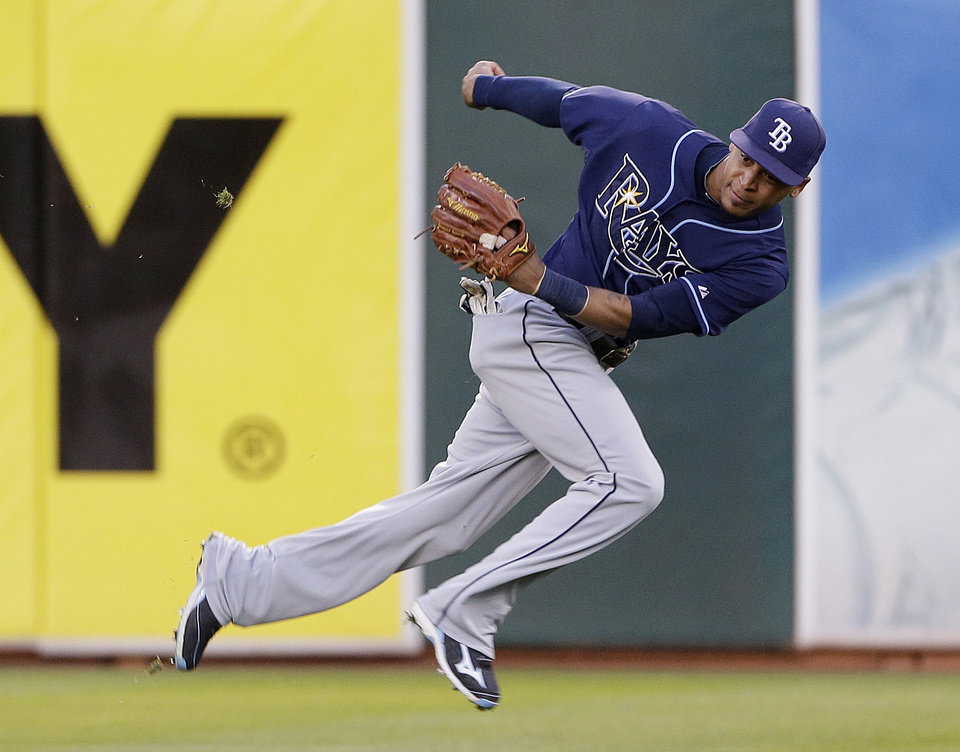 Photo - Tampa Bay Rays right fielder Wil Myers catches a fly ball hit by the Oakland Athletics' Yoenis Cespedes during the fourth inning of their baseball game Saturday, Aug. 31, 2013, in Oakland, Calif. (AP Photo/Eric Risberg)