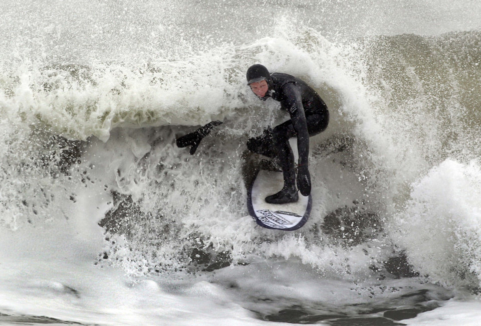 Photo - Jack Keefe surfs in the Atlantic Ocean on the coast of Hampton, N.H., after a winter storm kicked up the surf, Friday, Jan. 3, 2014. (AP Photo/Jim Cole)