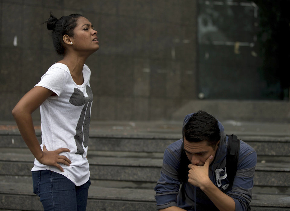 Photo - A female student cries after learning that fellow students maintaining a camp near the United Nations headquarters, were arrested in a pre-dawn raid, in Caracas, Venezuela, Thursday, May 8, 2014. Hundreds of security forces broke up four camps maintained by student protesters, arresting more than 200 people. The camps consisting of small tents were installed more than a month ago in front of the UN building and other anti-government strongholds in the capital to protest against President Nicolas Maduro's government. (AP Photo/Fernando Llano)