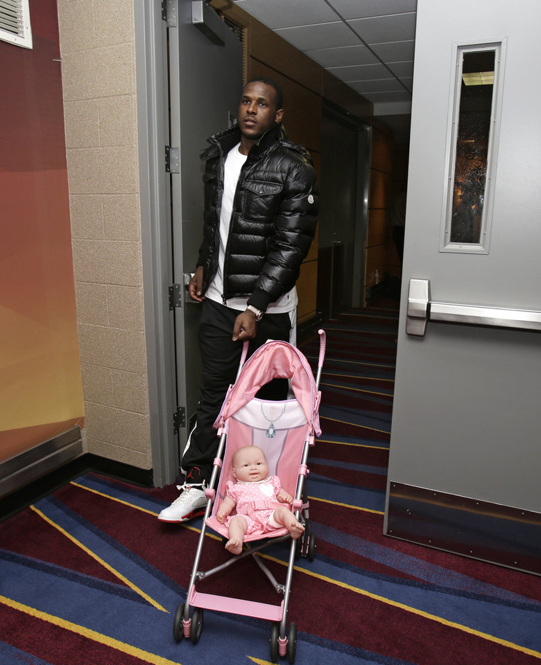 Photo - In this photo taken Wednesday, Feb. 27, 2013, Cleveland Cavaliers' Dion Waiters walks with a doll in a stroller, given to him earlier in the season by coach Byron Scott for rookie initiation, after an NBA basketball game against the Toronto Raptors in Cleveland. With one of the NBA's youngest rosters and a brutal schedule, the Cavaliers took their lumps in the first two months of the season. It toughened them up, and now a group led by 20-year-old star Kyrie Irving is developing into a team to be reckoned with in the future.(AP Photo/Tony Dejak)