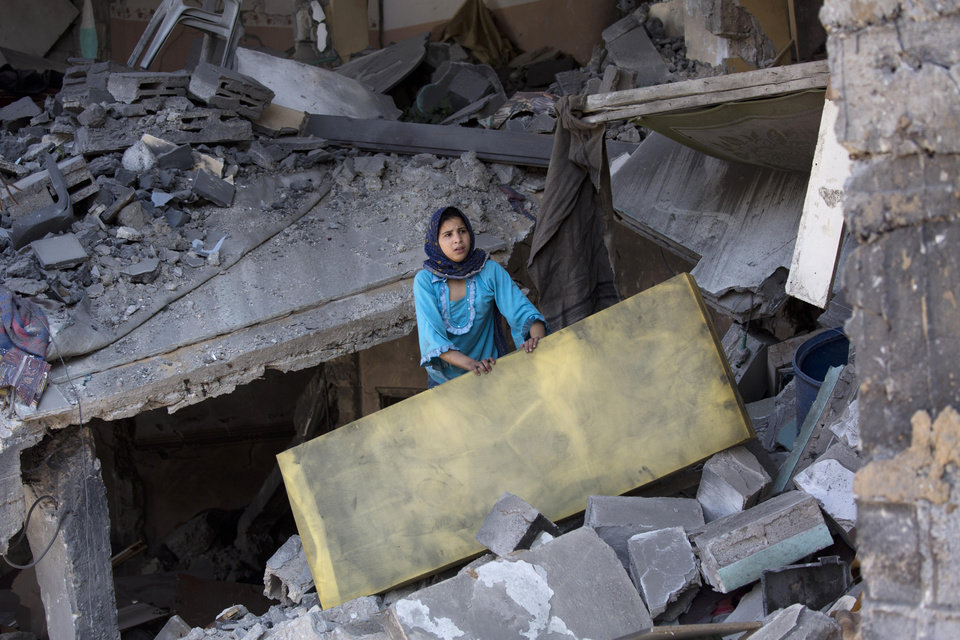 Photo - A Palestinian girl salvages a mattress from a destroyed house in the heavily bombed Gaza City neighborhood of Shijaiyah, close to the Israeli border, Friday, Aug. 1, 2014.(AP Photo/Dusan Vranic)