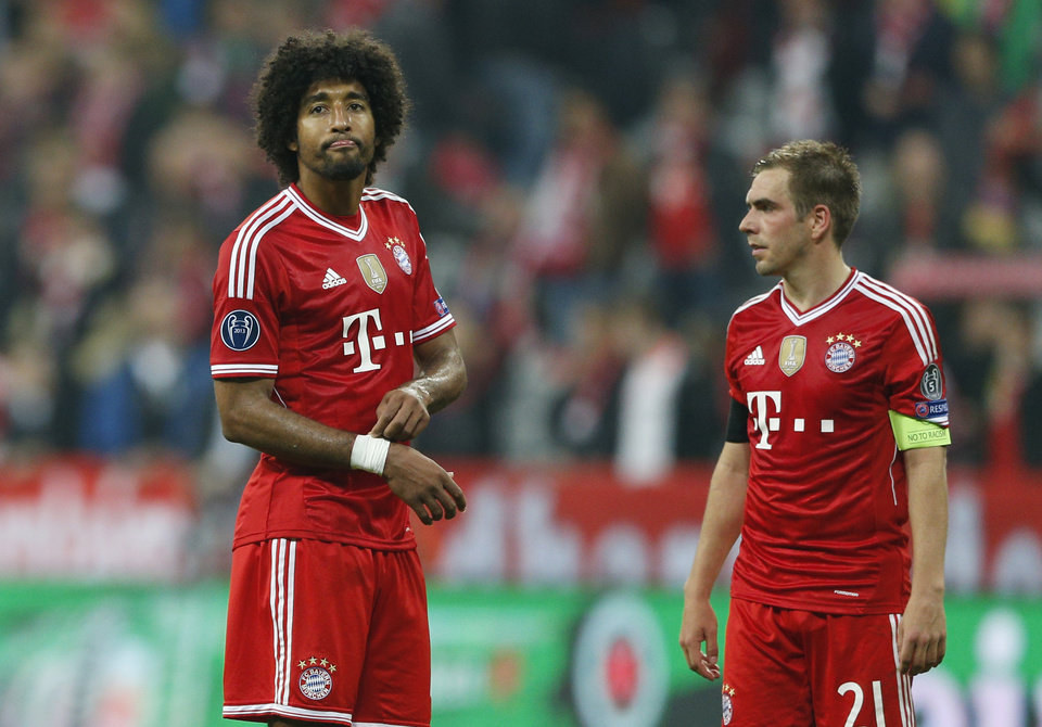 Photo - Bayern's Dante, left, and Philipp Lahm look disappointed after losing the Champions League semifinal second leg soccer match between Bayern Munich and Real Madrid at the Allianz Arena in Munich, southern Germany, Tuesday, April 29, 2014. (AP Photo/Matthias Schrader)