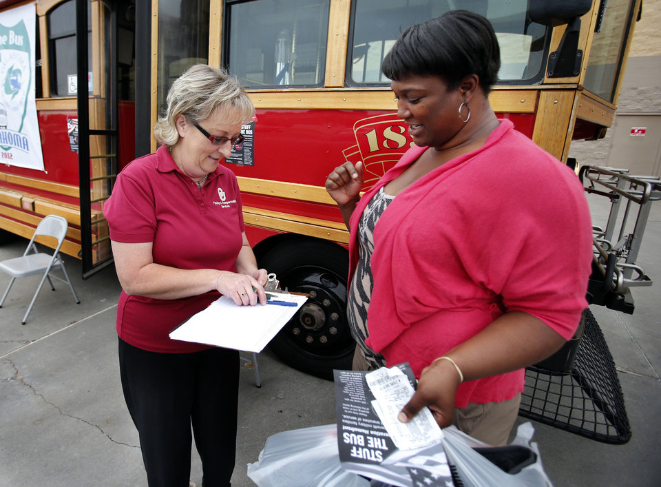 "Mackenzie Young, right, of Midwest City, donates a gift card as Cleveland Area Rapid Transit employee Betty Love attempts to ""Stuff the Bus"" in Norman on Thursday. Donations were being gathered to support Oklahoma military families. PHOTO BY STEVE SISNEY, THE OKLAHOMAN"