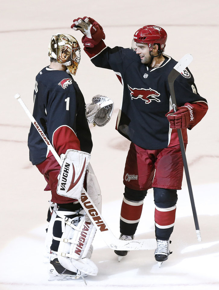 Photo - Phoenix Coyotes' Thomas Greiss (1), of Germany, celebrates his shutout against the Los Angeles Kings with teammate David Schlemko (6) after an NHL hockey game Tuesday, Jan. 28, 2014, in Glendale, Ariz.  The Coyotes defeated the Kings 3-0. (AP Photo/Ross D. Franklin)
