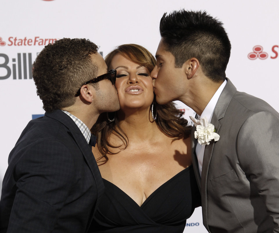 Photo - FILE - In this April 26, 2012, file photo, Singer Jenni Rivera, center, is kissed by singers Nacho, left, and Chino, right, as they walk the red carpet at the Latin Billboard Awards in Coral Gables, Fla. The wreckage of a small plane believed to be carrying Mexican-American music superstar Jenni Rivera was found in northern Mexico on Sunday, Dec. 9, 2012, and there are no apparent survivors, authorities said.  (AP Photo/Wilfredo Lee, file)