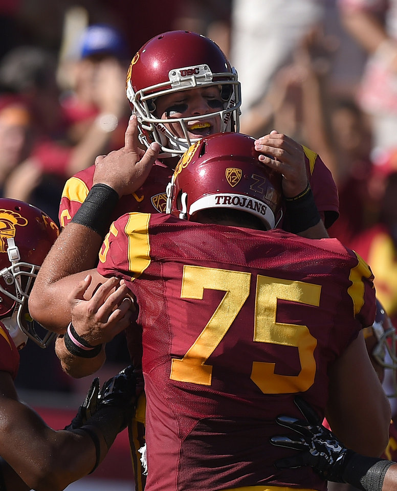 Photo - Southern California quarterback Cody Kessler, top, celebrates his touchdown with center Max Tuerk during they first half of an NCAA college football game against Fresno State, Saturday, Aug. 30, 2014, in Los Angeles. (AP Photo/Mark J. Terrill)