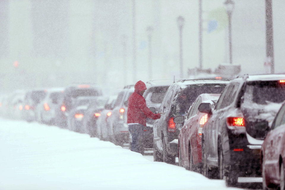 Photo - A man gets out of his car to clear the windows as traffic is at a standstill on John F Kennedy Boulevard during a winter snowstorm Tuesday, Jan. 21, 2014, in Philadelphia. A storm is sweeping across the Mid-Atlantic and New England. The National Weather Service said the storm could bring 8 to 12 inches of snow to Philadelphia and New York City, and more than a foot in Boston.  (AP Photo/Matt Rourke)