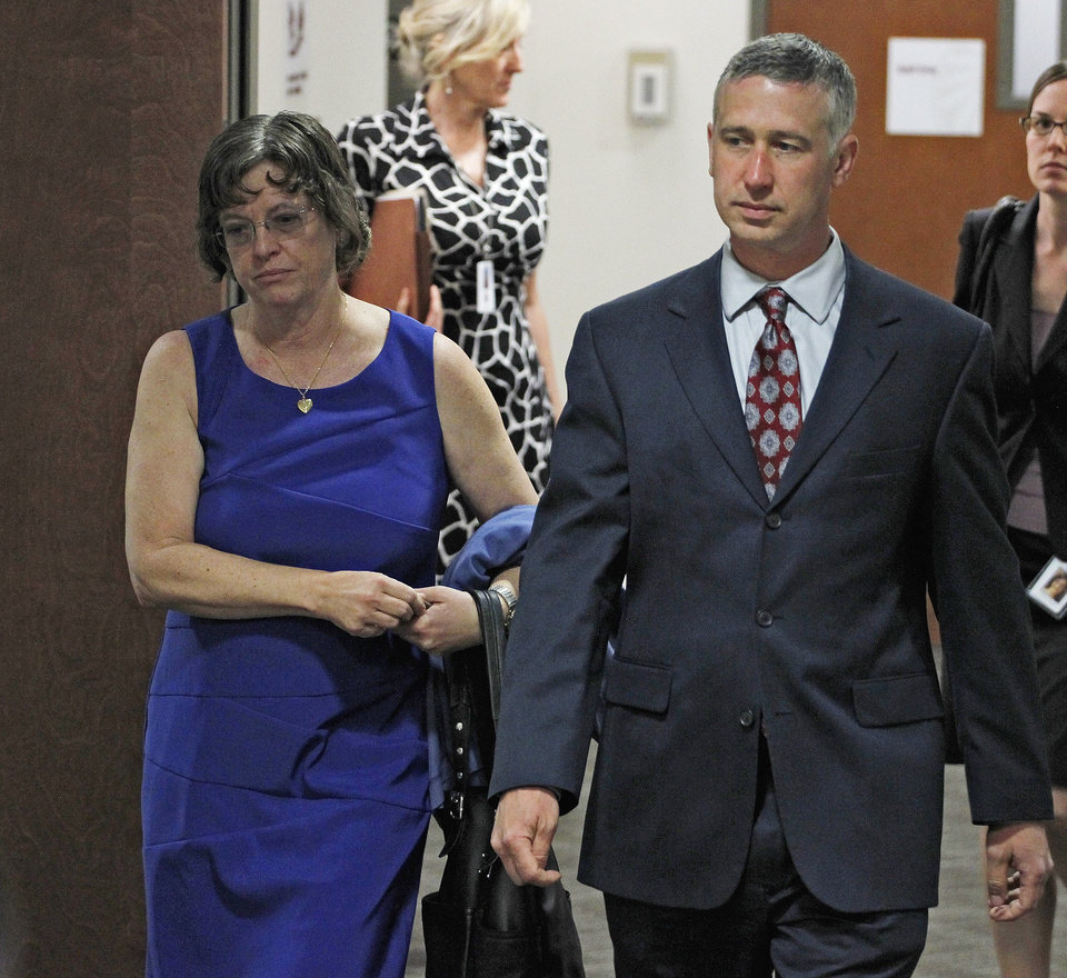 Photo - Arlene Holmes, left, mother of Aurora theater shooting suspect James Holmes, is escorted by a member of the defense team as she arrives for a hearing Monday, May 13, 2013, in Centennial, Colo., where her son asked a judge to enter a plea of not guilty by reason of insanity. (AP Photo/Brennan Linsley)