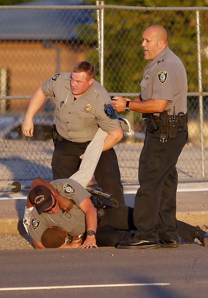 Photo - Oklahoma City Police arrests a man during a protest near the intersection of 23rd and Classen in Oklahoma City, Saturday, May 30, 2020. The protest was in response to the death of George Floyd. [Sarah Phipps/The Oklahoman]
