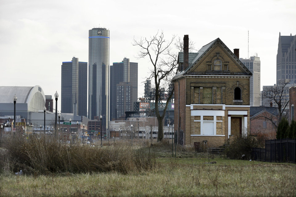 In a photo from Monday, Dec. 2, 2013, an empty field in Brush Park, north of Detroit's downtown is shown with an abandoned home. Detroit, which on Thursday, July 18, 2013, filed the largest municipal bankruptcy case in American history, owes as much as $20 billion to banks, bondholders and pension funds. The city can get rid of its gargantuan debt, but a bankruptcy judge can�t bring back residents or raise its dwindling revenue. (AP Photo/Carlos Osorio, File)