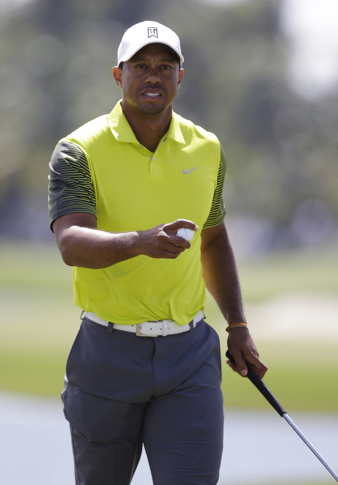 Photo - Tiger Woods holds the ball ball after making par on the 10th hole during the second round of the Cadillac Championship golf tournament Friday, March 7, 2014, in Doral, Fla. (AP Photo/Wilfredo Lee)