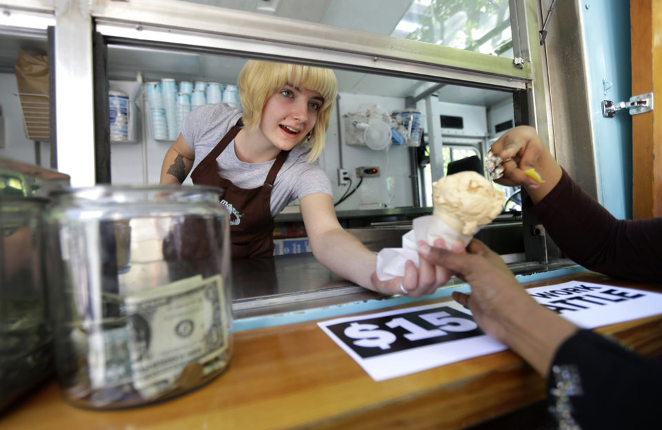 Photo - Caitlyn Faircloth, a worker with Molly Moon's Homemade Ice Cream, hands out free ice cream next to a tip jar, Monday, June 2, 2014, at a rally celebrating the passage of a $15 minimum wage measure outside Seattle City Hall in Seattle. The Seattle City Council passed a $15 minimum wage measure, Monday, but not until after debate over how long businesses will have to phase in the measure, and how tips, benefits, and other forms of compensation will be considered. (AP Photo/Ted S. Warren)