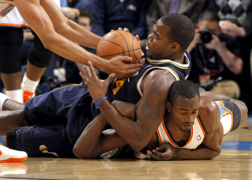 Photo - Oklahoma City's Serge Ibaka and the Jazz' Paul Millsap scramble for a loose ball during the NBA game between the Oklahoma City Thunder and Utah Jazz, Wednesday, March 23, 2011, at the Oklahoma City Arena. Photo by Sarah Phipps, The Oklahoman