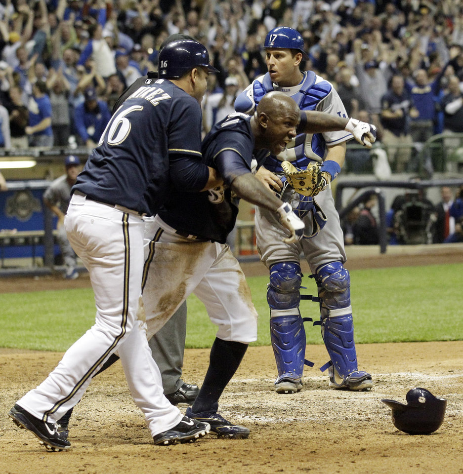 Photo -   Los Angeles Dodgers catcher A.J. Ellis, right, reacts as Milwaukee Brewers' Nyjer Morgan, center, celebrates with Aramis Ramirez (16) after Morgan scored from third on a sacrifice fly by Ryan Braun during the 10th inning of a baseball game on Wednesday, April 18, 2012, in Milwaukee. The Brewers won 3-2. (AP Photo/Morry Gash)