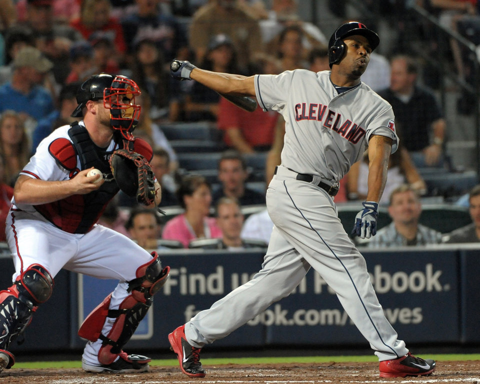 Photo - Cleveland Indians' Michael Bourn, right, strikes out swinging in front of Atlanta Braves catcher Brian McCann during the fifth inning of a baseball game at Turner Field, Tuesday, Aug. 27, 2013, in Atlanta. (AP Photo/David Tulis)