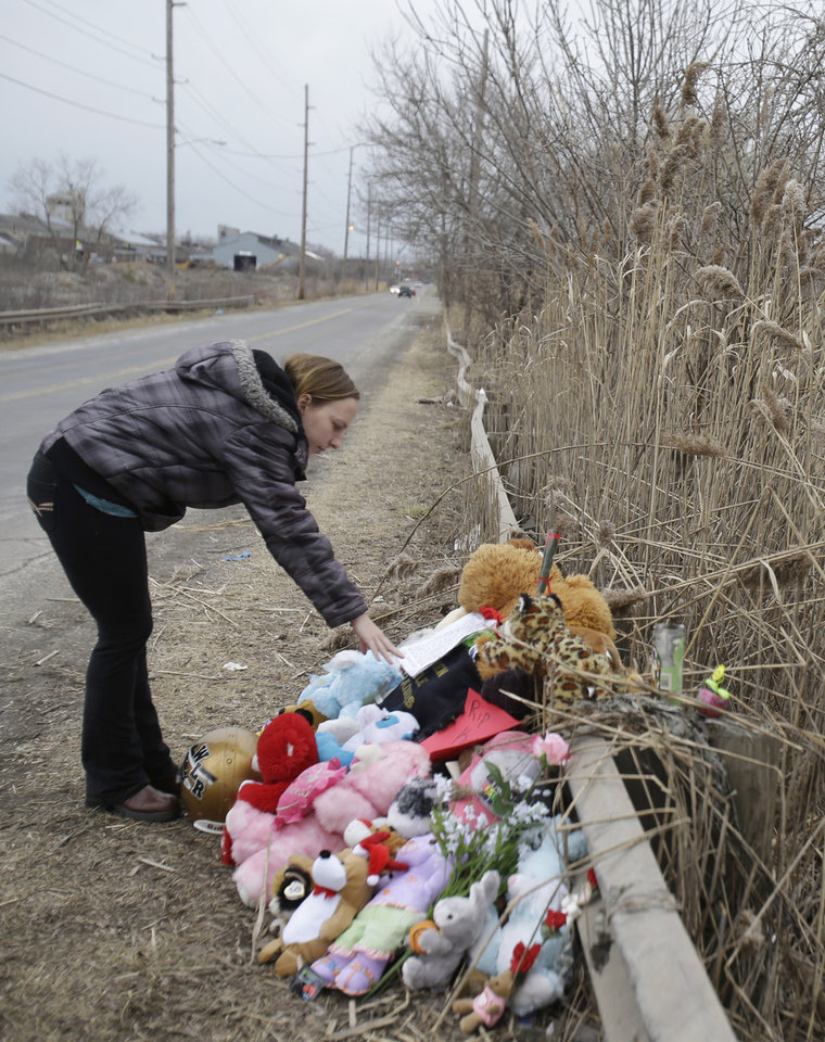 Photo - Shannon Whetstone reads notes left at the scene where six teens died early Sunday in Warren, Ohio, on Monday, March 11, 2013. Two teens who escaped a crash that killed six friends in a swampy pond wriggled out of the wreckage by smashing a rear window and swimming away from the SUV, a state trooper said Monday. (AP Photo/Tony Dejak)