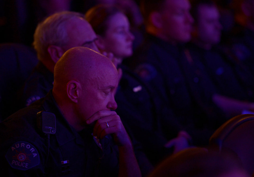 Photo - Aurora Police Officer Mike Hawkins, a 18 year veteran and first responder to the shooting sits with other Aurora Police officers during the reopening and remembrance ceremony at the Century Aurora cinema, formerly the Century 16, Thursday, Jan. 17, 2013 in Aurora, Colo. The cinema is where 12 people were killed and dozens injured in a shooting rampage last July. (AP Photo/The Denver Post, RJ Sangosti, Pool)