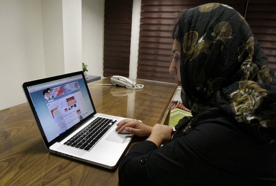 Iranian photojournalist Maryam Rahmanian checks the newly launched website of Iran\'s Intelligence Ministry, in Tehran, Iran, Wednesday, Oct. 10, 2012. A glimpse into the shadow world of Iran\'s main spy agency is now a click away. In an unexpected display of outreach, the Intelligence Ministry now hosts a website with addresses of provincial offices, appeals for tips and anti-American essays that mock rising obesity rates, large prison populations and school shootings. (AP Photo/Vahid Salemi)