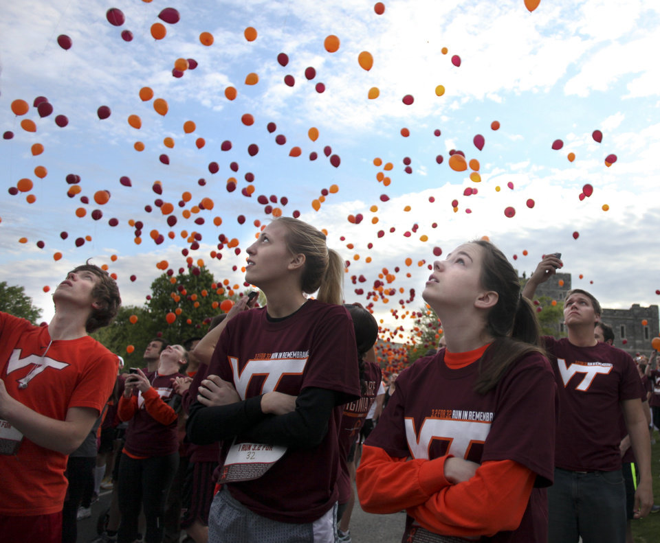Photo -   Paige Eckerd, right, and Kristy McCain, center, look skyward at released balloons at the start of a Run in Remembrance on the Virginia Tech campus in Blacksburg, Va. on Saturday, April 14, 2012. The 3.2-mile Run in Remembrance for the victims of the April 16, 2007, Virginia Tech shootings had about 6,500 participants registered in advance for the event in honor of the 32 killed in the deadliest mass shooting in modern U.S. history. (AP Photo/The Roanoke Times, Matt Gentry)