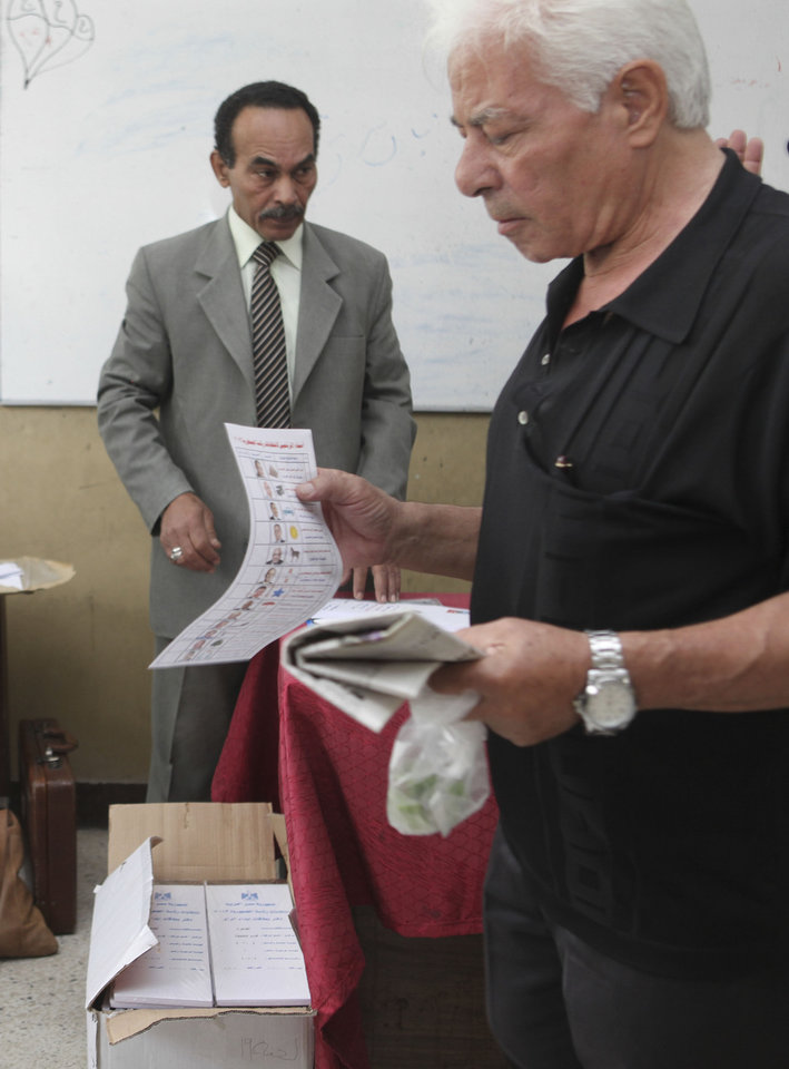 Photo -   An Egyptian receives a ballot inside a polling station the Sayeda Aisha neighborhood of Cairo Egypt, Wednesday, May 23, 2012. Egyptians went to the polls on Wednesday morning to elect a new president after the fall of ex-President Hosni Mubarak last year.(AP Photo/Thomas Hartwell)