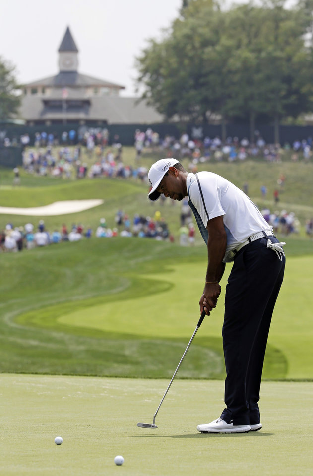 Photo - Tiger Woods putts on the first hole during a practice round for the PGA Championship golf tournament at Valhalla Golf Club on Wednesday, Aug. 6, 2014, in Louisville, Ky. The tournament is set to begin on Thursday. (AP Photo/David J. Phillip)