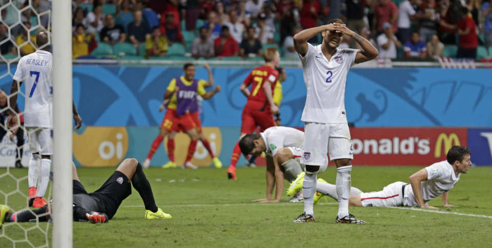 Photo - US players react after Belgium's Kevin De Bruyne, centre, scored the opening goal during the World Cup round of 16 soccer match between Belgium and the USA at the Arena Fonte Nova in Salvador, Brazil, Tuesday, July 1, 2014. (AP Photo/Julio Cortez)
