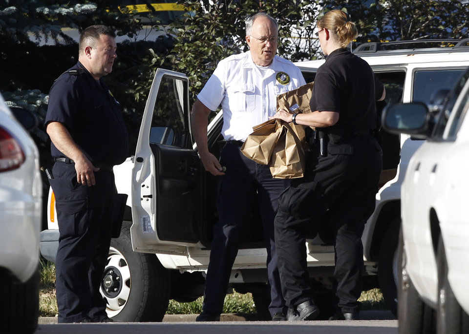 Photo - Officers load bags of evidence into a car outside the Century 16 theater east of the Aurora Mall in Aurora, Colo., on Friday, July 20, 2012. A shooting took place in the theater in which at least 12 people died and scores were injured during the premiere showing of