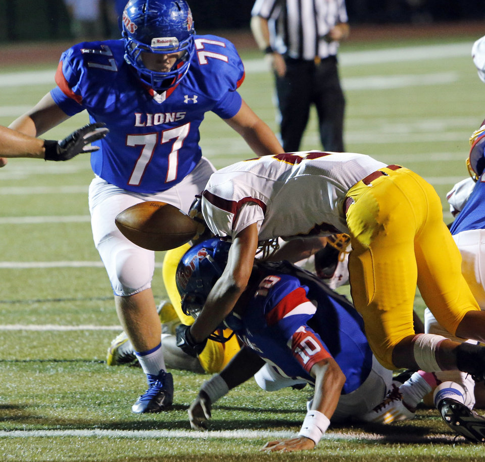 Moore\'s K. J. Carrethers fumbles near the goal line and the ball is recovered by teammate David Johnson (77) as the Moore High School Lions play the Putnam City North Panthers in high school football on Thursday, Oct. 3, 2013, in Moore, Okla. Photo by Steve Sisney, The Oklahoman