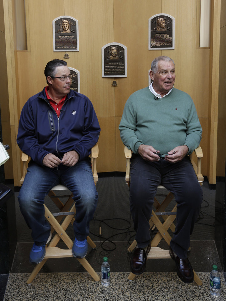 Photo - Former Atlanta Braves pitcher Greg Maddux, left, and former manager Bobby Cox talk to reporters after their orientation visit at the Baseball Hall of Fame on Monday, March 24, 2014, in Cooperstown, N.Y. They will be inducted to the hall in July. (AP Photo/Mike Groll)