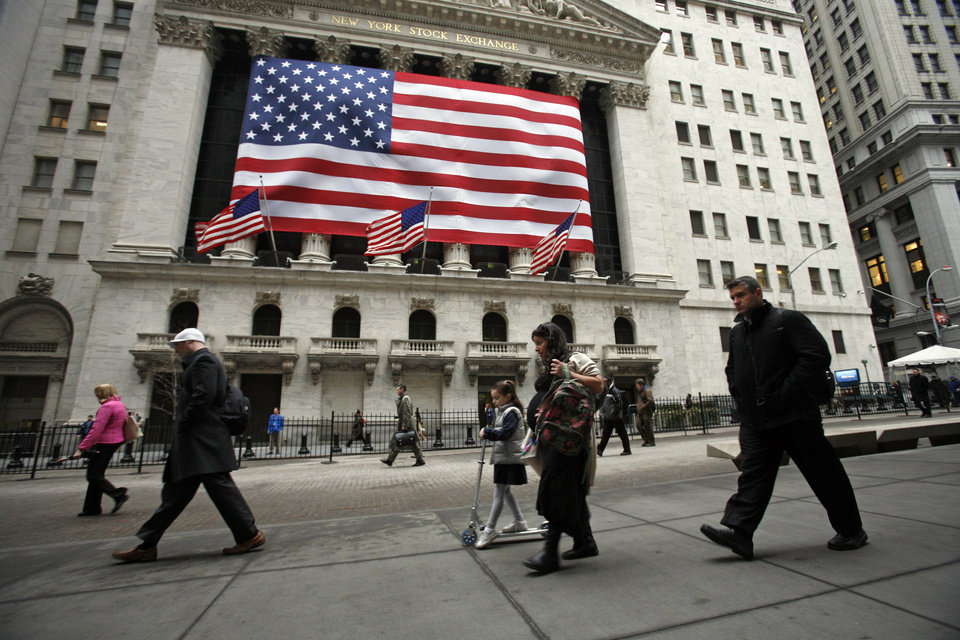 Photo - People pass in front of the New York Stock Exchange in this Monday, March 9, 2009 photo. Worries over Russian troops amassing near the Ukraine border caused a sharp sell-off in global stock markets on Wednesday Aug. 6, 2014. (AP Photo/Mark Lennihan)