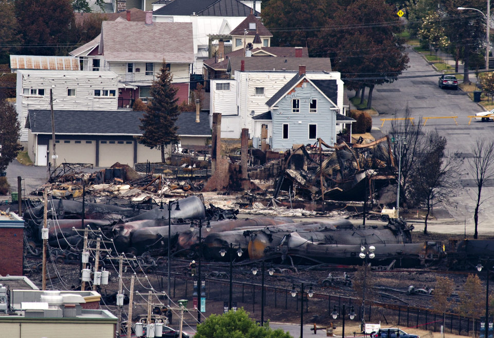 Photo - Charred tanker cars are piled up in Lac-Megantic, Quebec, Tuesday, July 9, 2013.   Investigators are looking for the cause of the fiery oil train derailment Saturday that led to the explosions that killed at least 13 people. (AP Photo/THE CANADIAN PRESS,Jacques Boissinot )