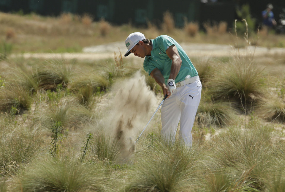Photo - Rickie Fowler hits out of the long grass on the 18th hole during a practice round for the U.S. Open golf tournament in Pinehurst, N.C., Wednesday, June 11, 2014. The tournament starts Thursday. (AP Photo/Charlie Riedel)