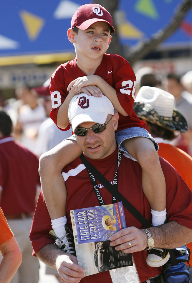 Photo - FANS: Zach Riddle, 6, gets a lift from his father Kevin Riddle of Tulsa through the midway at the State Fair of Texas before the University of Oklahoma Sooners (OU) college football game against the University of Texas (UT), in the Red River Shootout at the Cotton Bowl, on Saturday, Oct. 7, 2006, in Dallas, Tex.    by Steve Sisney, The Oklahoman  ORG XMIT: KOD