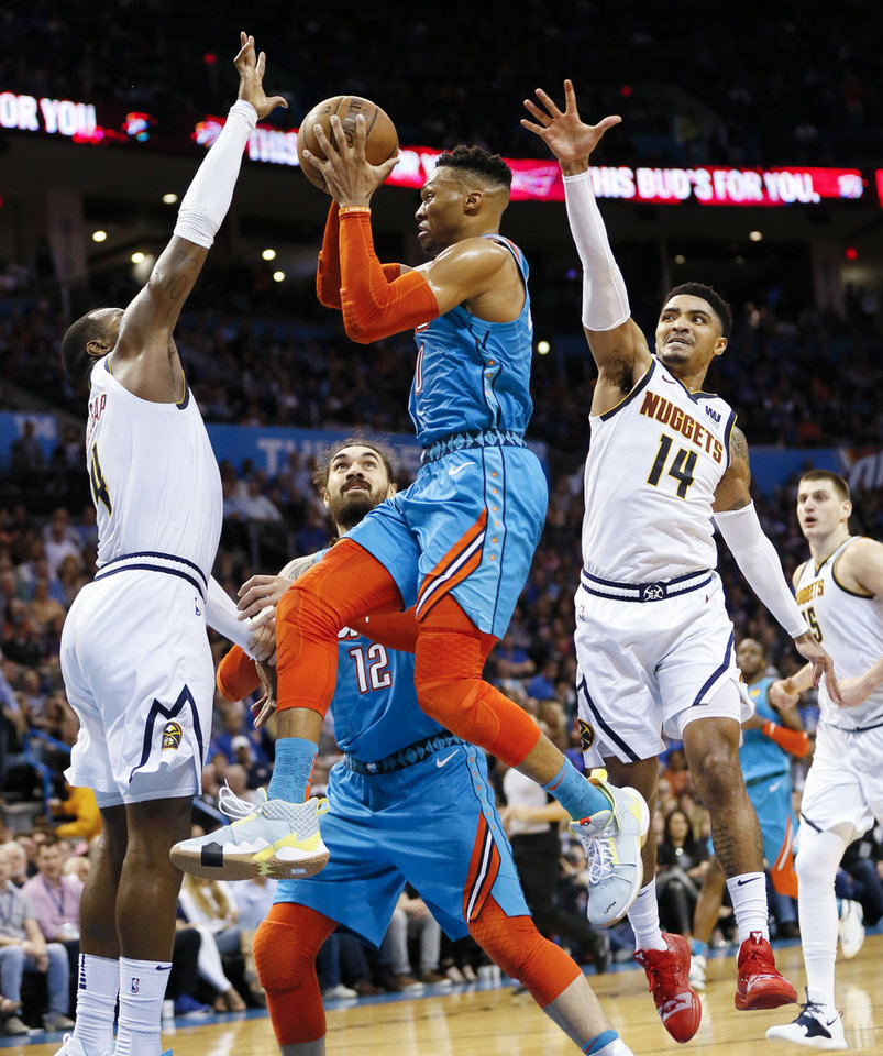Photo - Oklahoma City's Russell Westbrook (0) drives to the basket between Denver's Paul Millsap (4), left, and Gary Harris (14) as Oklahoma City's Steven Adams (12) looks on in the second quarter during an NBA basketball game between the Denver Nuggets and the Oklahoma City Thunder at Chesapeake Energy Arena in Oklahoma City, Friday, March 29, 2019. Photo by Nate Billings, The Oklahoman
