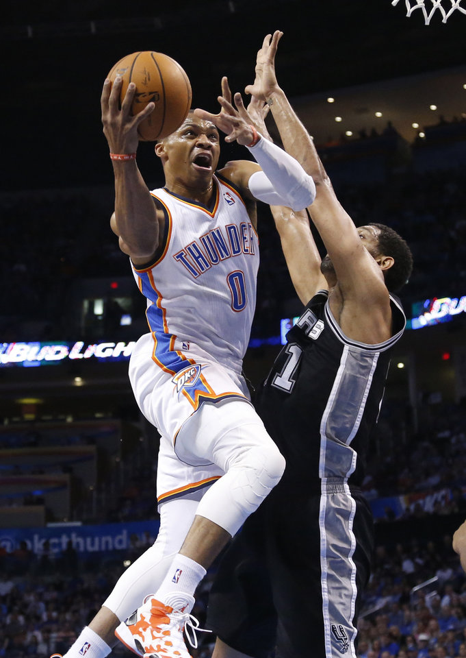 Photo - Oklahoma City Thunder guard Russell Westbrook (0) goes up to shoot as San Antonio Spurs forward Tim Duncan defends during the first quarter of an NBA basketball game in Oklahoma City, Thursday, April 3, 2014. (AP Photo/Sue Ogrocki)