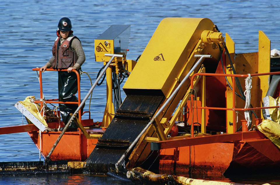 Photo - FILE - In this April 21, 1989, file photo, a skimmer is used for shoreline oil in Naked Island, Alaska. It collects the oil from off the water surface. The conveyor belt moves the oil onto a barge for storage. Nearly 25 years after the Exxon Valdez oil spill off the coast of Alaska, some damage heals, some effects linger in Prince William Sound. (AP Photo/Rob Stapleton, File)